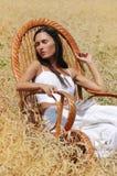 Menina bonita nova que dorme em uma cadeira no campo de trigo foto de stock royalty free