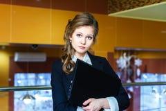 Menina bonita nova que está no escritório e que guarda um portátil Fotografia de Stock