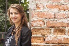 Menina bonita nova que está em uma rua perto da parede de tijolo Fotografia de Stock