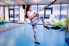 Menina bonita nova que exercita com as correias da aptidão no gym imagem de stock