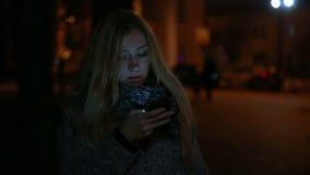 Menina bonita nova que fala em um telefone celular e filme