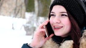 Menina bonita nova que fala pelo telefone celular na floresta do inverno vídeos de arquivo