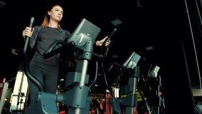 Menina bonita nova que faz cardio- exerc?cios no simulador video estoque