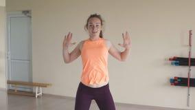 A menina bonita nova que faz a dança exercita no gym ou no estúdio Movimento lento conceito da aptidão, do esporte, da dança e do