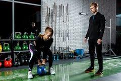 Menina bonita nova que faz um exercício com pesos sob a orientação de um treinador Imagem de Stock Royalty Free