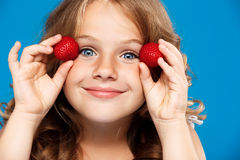 Menina bonita nova que guarda a morango sobre o fundo azul foto de stock