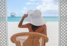 Menina bonita nova que guarda o chapéu que senta-se na praia que olha ho Imagens de Stock Royalty Free