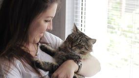 Menina bonita nova que joga com um gato na janela video estoque