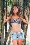 Menina bonita nova que levanta com as árvores do bamoo, conceito quente da forma do verão Imagens de Stock Royalty Free