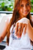 Menina bonita nova que mostra sua mão com o anel de prata Foto de Stock Royalty Free