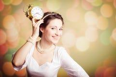 Menina bonita nova que mostra um despertador no bokeh Foto de Stock Royalty Free