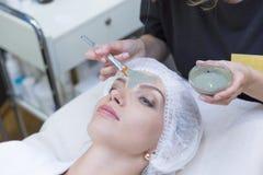 Menina bonita nova que recebe a máscara facial do doutor no salão de beleza dos termas - dentro foto de stock