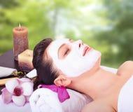 Menina bonita que recebe a máscara facial cor-de-rosa Fotografia de Stock Royalty Free