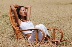 Menina bonita nova que relaxa em uma cadeira fotos de stock royalty free