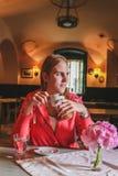 Menina bonita nova que senta-se em um café de pensamento e bebendo do café fotografia de stock