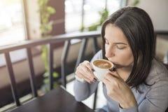 Menina bonita nova que senta-se na cafetaria e que aprecia o café fotos de stock
