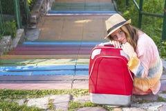 Menina bonita nova que senta-se na rua com mala de viagem vermelha Fotos de Stock Royalty Free