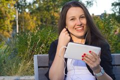 Menina bonita nova que senta-se no banco no parque e que escuta Imagens de Stock