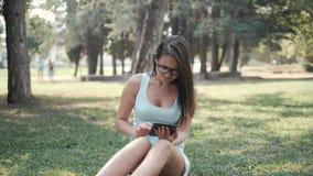 Menina bonita nova que senta-se no gramado no parque usando o PC da tabuleta, conceito em linha da compra video estoque