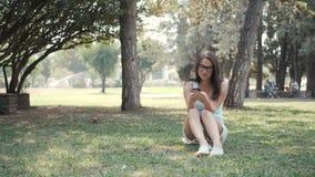 Menina bonita nova que senta-se no gramado no parque usando o telefone, conceito em linha da compra video estoque