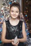 Menina bonita nova que sorri e que guarda uma árvore de Natal No vestido preto feliz Fotos de Stock Royalty Free