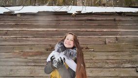 A menina bonita nova que tem a neve de sopro do divertimento na câmera no inverno veste-se no fundo de uma casa de madeira no fotografia de stock royalty free