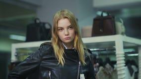 Menina bonita nova que tenta em um casaco de cabedal na loja filme