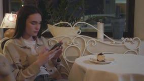 Menina bonita nova que toma fotos no smartphone do bolo de dar água na boca fresco com as decorações na tabela vídeos de arquivo