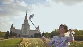 Menina bonita nova que toma a imagem da vara do selfie feliz no dia ensolarado filme