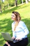 Menina bonita nova que trabalha no portátil exterior, encontrando-se na grama, caucasian 20 anos velho Imagens de Stock