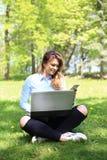 Menina bonita nova que trabalha no portátil exterior, encontrando-se na grama, caucasian 20 anos velho Fotografia de Stock Royalty Free