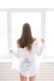 Menina bonita nova que unclothing uma camisa branca dos men's perto da janela fotos de stock