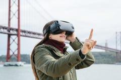 Menina bonita nova que veste vidros da realidade virtual 25o da ponte de abril em Lisboa no fundo O conceito de Imagem de Stock