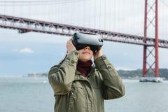 Menina bonita nova que veste vidros da realidade virtual 25o da ponte de abril em Lisboa no fundo O conceito de Imagem de Stock Royalty Free