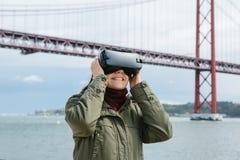 Menina bonita nova que veste vidros da realidade virtual 25o da ponte de abril em Lisboa no fundo O conceito de Fotografia de Stock