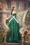 A menina bonita, nova, ruivo em um vestido medieval verde, escala as escadas ao castelo Photosession fantástico imagem de stock