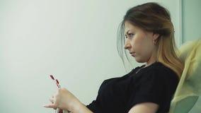 A menina bonita nova senta-se em uma cadeira, em um salão de beleza vídeos de arquivo