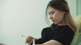 A menina bonita nova senta-se em uma cadeira, em um salão de beleza filme