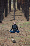 A menina bonita nova senta-se em uma posição de lótus na natureza em um conife Fotografia de Stock