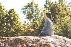 A menina bonita nova senta-se em uma rocha grande e admira-se a natureza imagens de stock royalty free