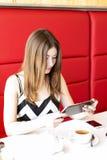 A menina bonita nova senta-se no café, dia ensolarado, guardando uma tabuleta, Imagem de Stock