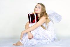 A menina bonita nova um anjo com um presente Imagens de Stock Royalty Free