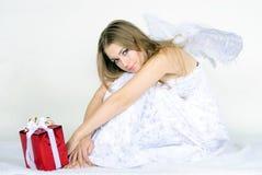 A menina bonita nova um anjo com um presente Fotos de Stock