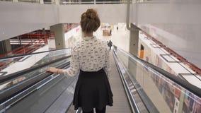 A menina bonita nova vai para baixo em uma escada rolante direta video estoque