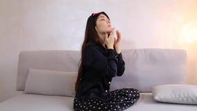 A menina bonita ocupa da pele da cara e faz ou faz os procedimentos cosméticos, sentando-se no sofá no quarto na noite vídeos de arquivo