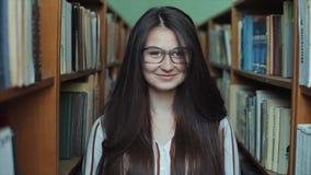 Menina bonita ofpretty do retrato na biblioteca com cabelo preto longo Estudante fêmea que estuda entre o lote dos livros no meio video estoque