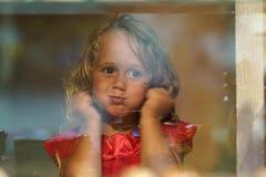 A menina bonita olha na janela de uma loja em OIA, e faz as caras engraçadas foto de stock royalty free