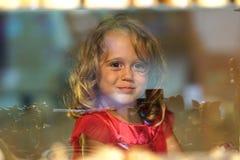 A menina bonita olha na janela de uma loja em OIA, e faz as caras engraçadas imagem de stock royalty free