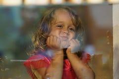 A menina bonita olha na janela de uma loja em OIA, e faz as caras engraçadas fotografia de stock royalty free