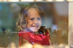 A menina bonita olha na janela de uma loja em OIA, e faz as caras engraçadas fotografia de stock